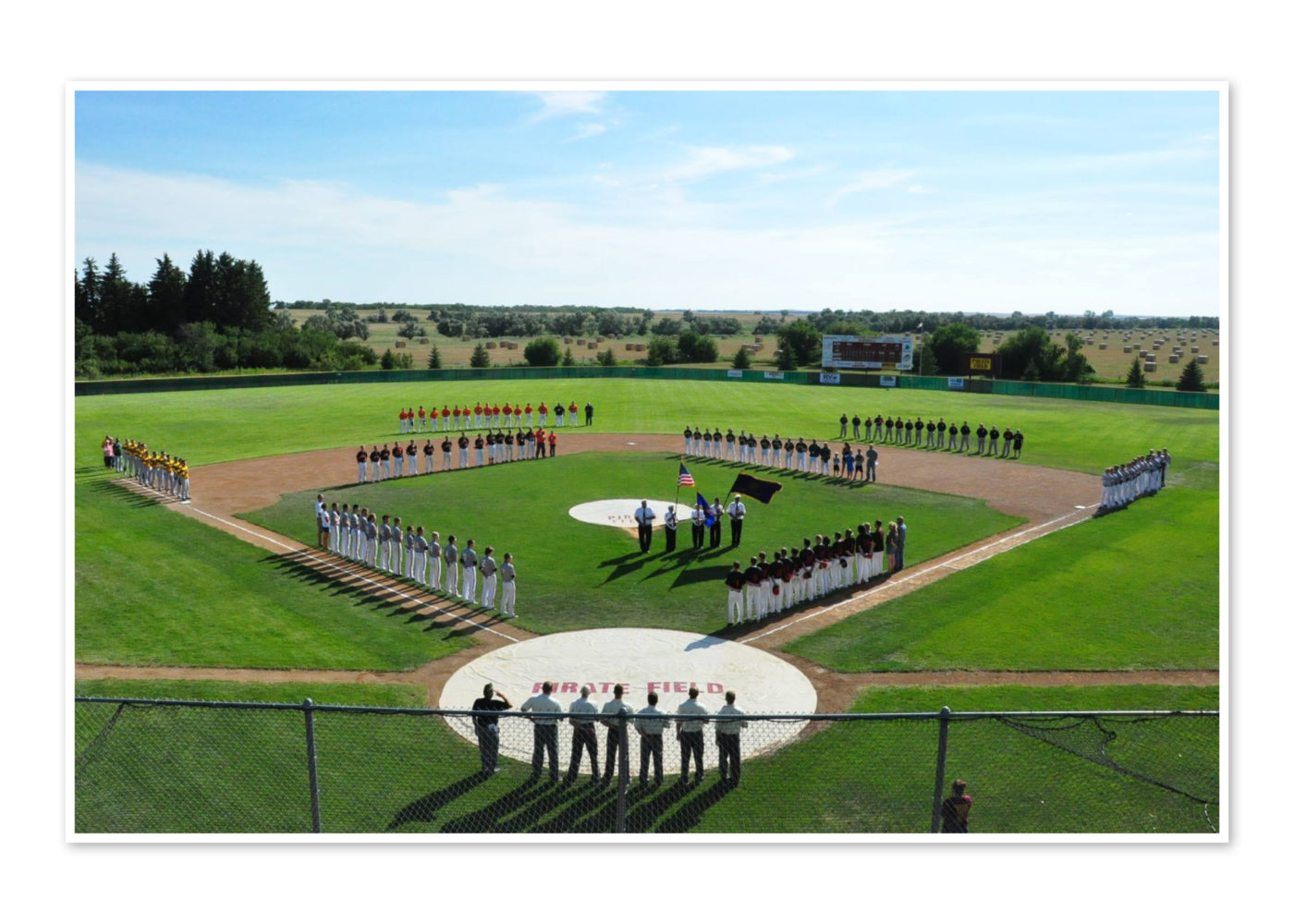 Several Legion baseball teams line the field, standing at attention for the national anthem