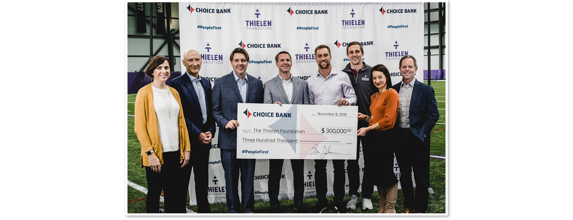 Choice Bank team members handing check for $300,000 to Adam Thielen and the The Thielen Foundation